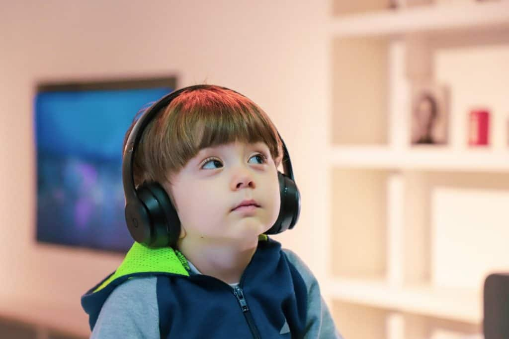 toddler wearing noise-cancelling headphones looking up