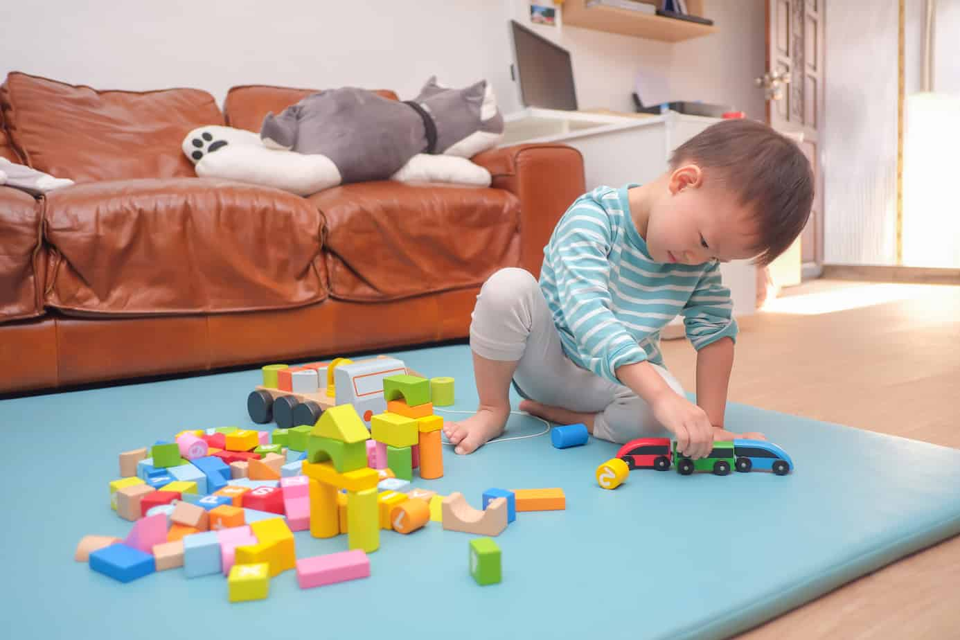 2 - 3 years old toddler boy child having fun playing with wooden building block toys indoor