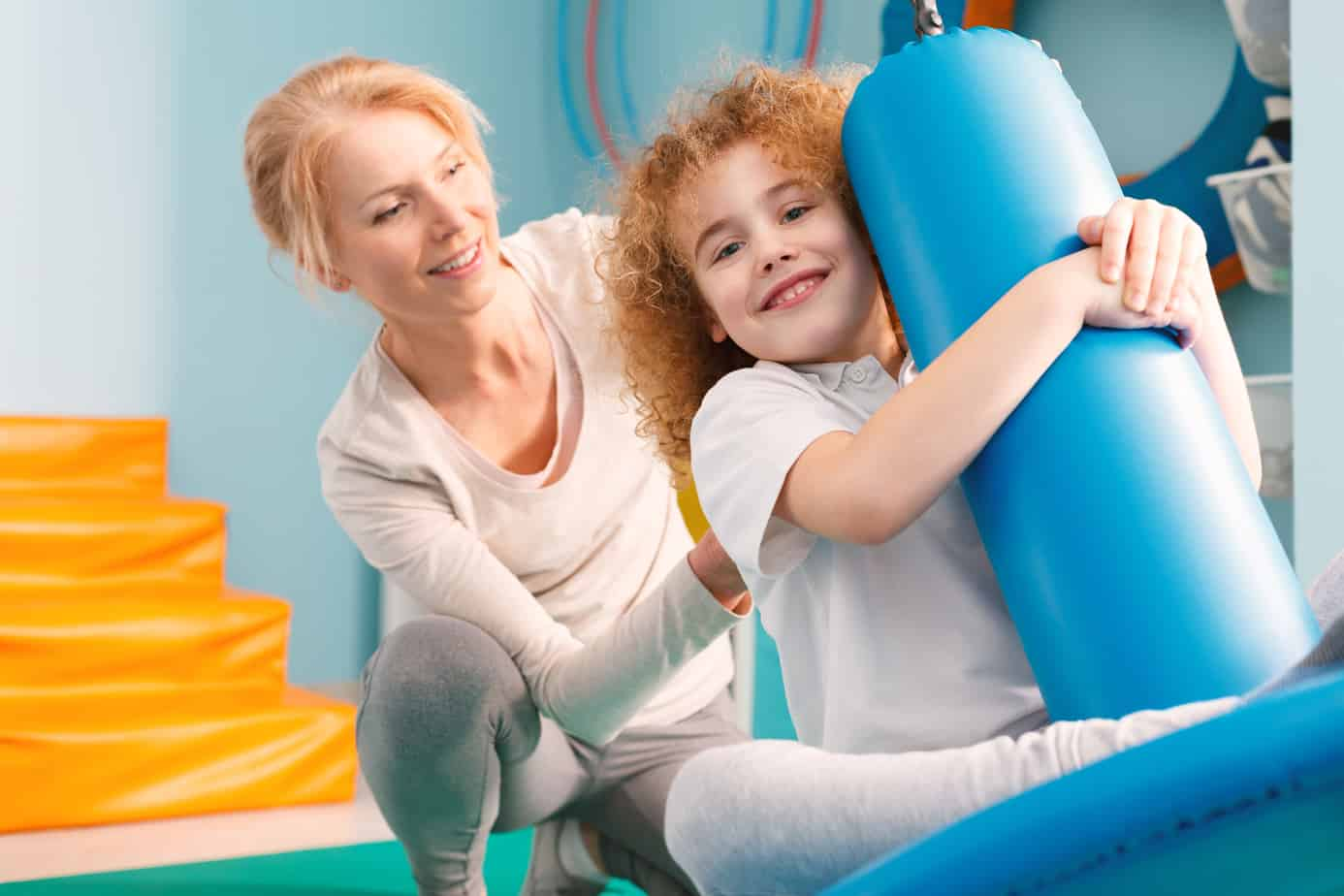 Smiling therapist watching a boy on disc swing during therapy session