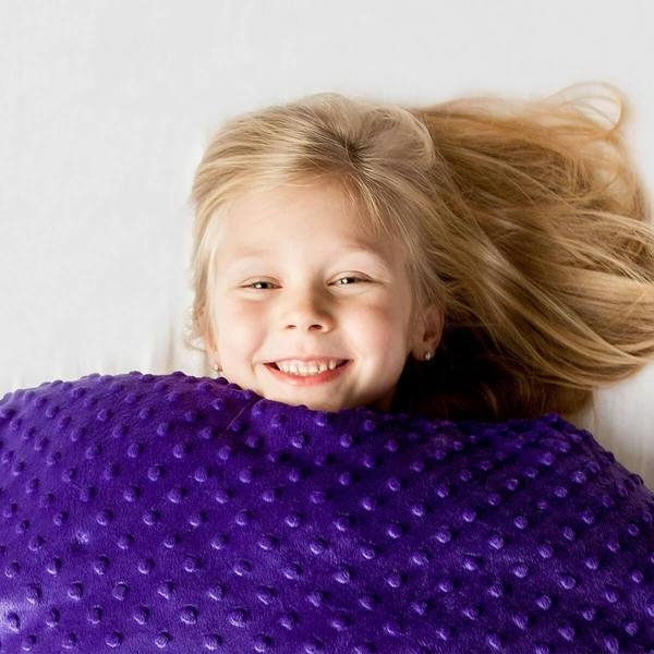 young girl smiling under a purple weighted blanket