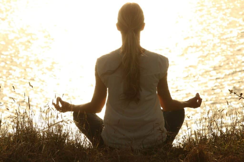Woman meditating by the lake, view from behind