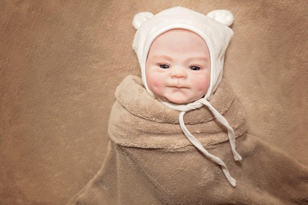 lifelike baby doll wrapped in blanket