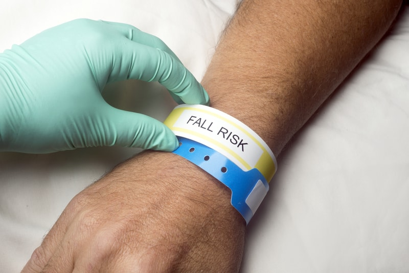 clinical's hand placing a falls risk bracelet around a patient's wrist