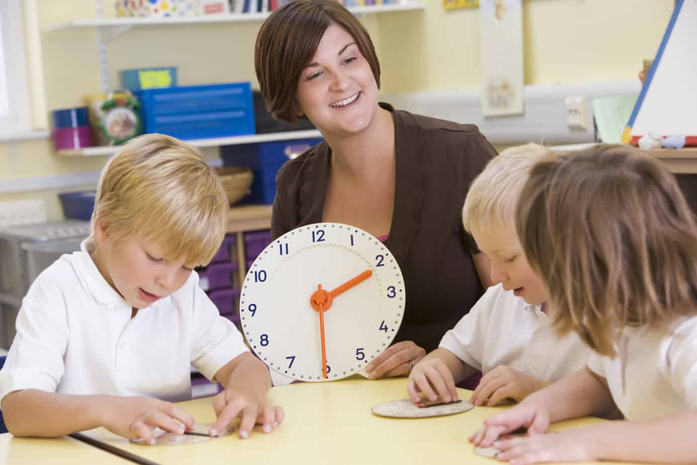 Teacher helping schoolchildren learn to tell time in primary cla