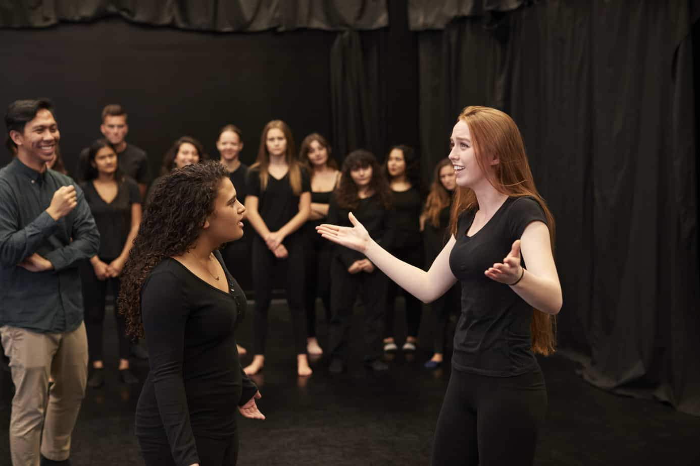 Teacher With Male And Female Drama Students At Performing Arts School In Studio Improvisation Class.